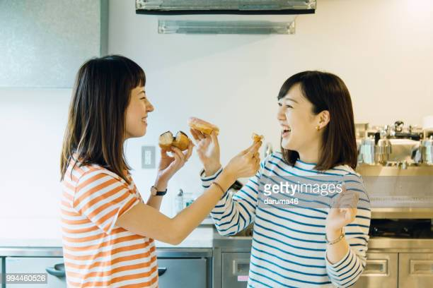 young women holding a donut in the kitchen.