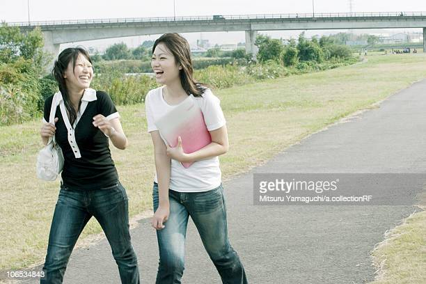 Young women holding a file and walking