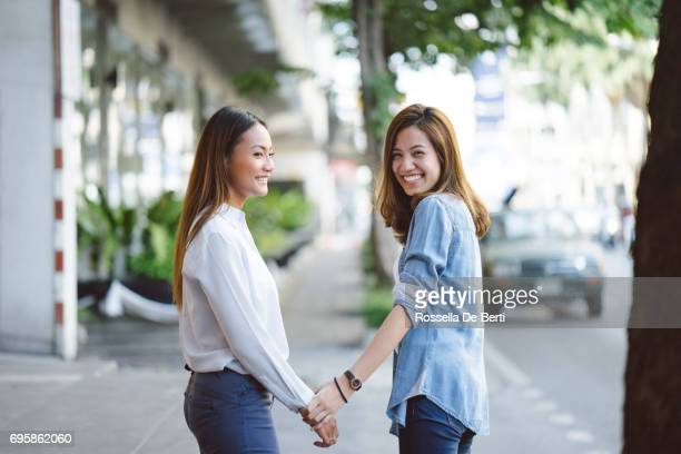 Young women holding hands outdoors, cityscape on background