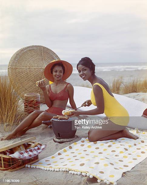 young women holding hot dog on beach, smiling - archival stock pictures, royalty-free photos & images