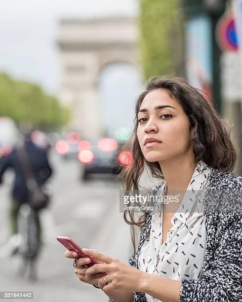 """Jeune femme tenant téléphone portable à la recherche de l """" hôtel"""