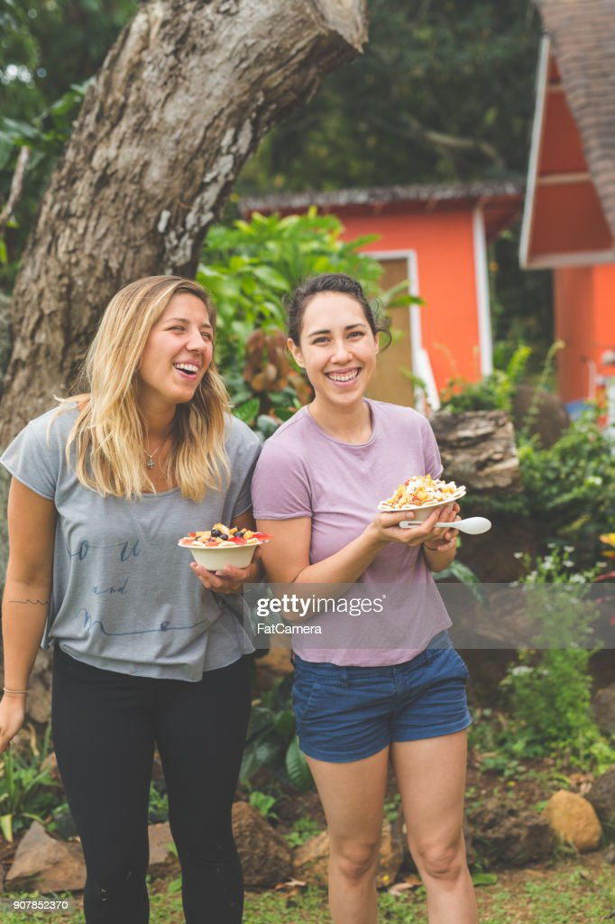 Young women holding smoothie bowls with fresh tropical fruit outdoors : Stock Photo