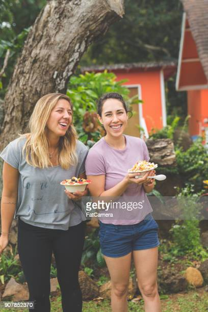 Young women holding smoothie bowls with fresh tropical fruit outdoors