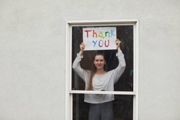 Young women holding up Thank You sign in window looking out