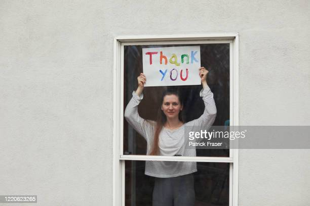 young women holding up thank you sign in window looking out - gratitude stock pictures, royalty-free photos & images