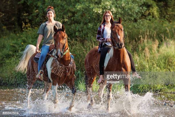 Young women horses riding in the river