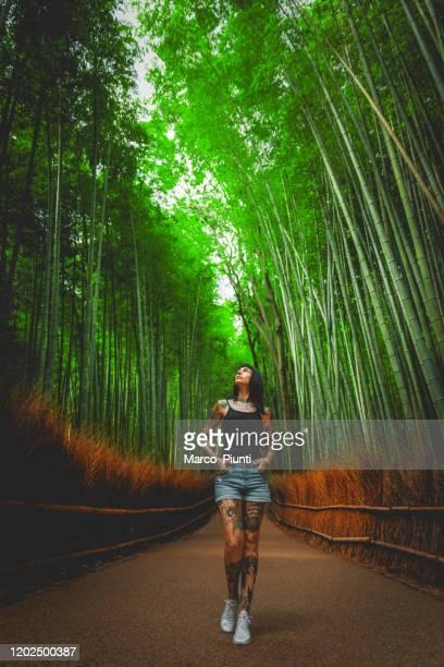 young women in arashiyama bamboo forest in kyoto, japan - arashiyama stock pictures, royalty-free photos & images