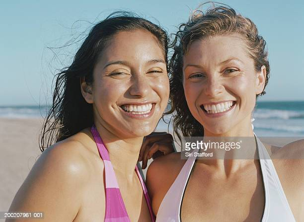 Young women in bathing suits on beach, smiling