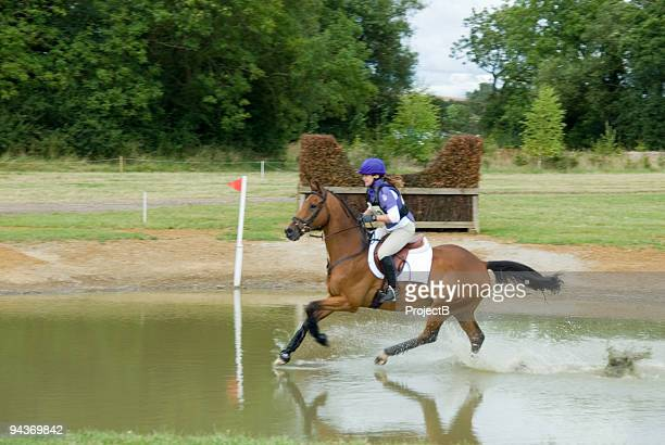 young women in cross country water jump - equestrian eventing stock pictures, royalty-free photos & images