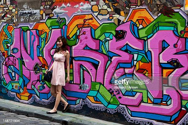 Young women in front of street art graffiti in Hosier Lane.