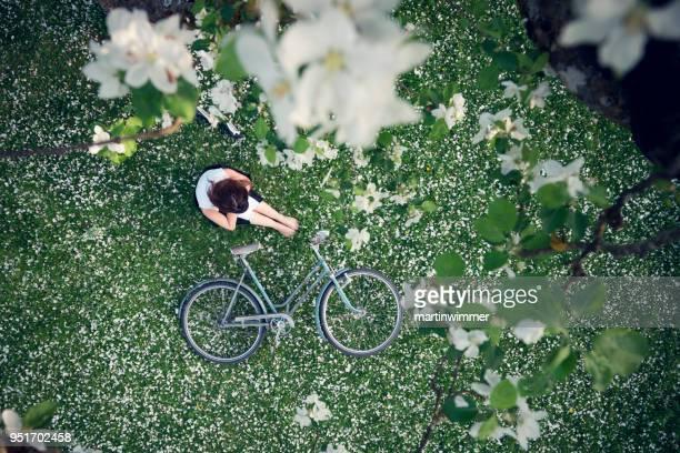 Junge Frauen in Rasen voller Apfelblüten