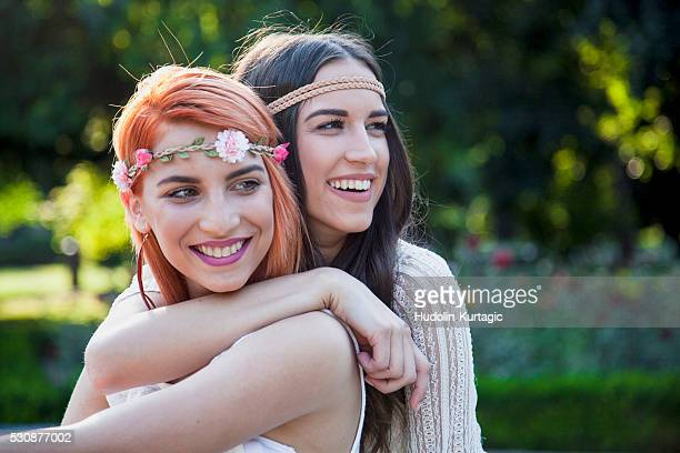 Young women in hippie style fashion embracing