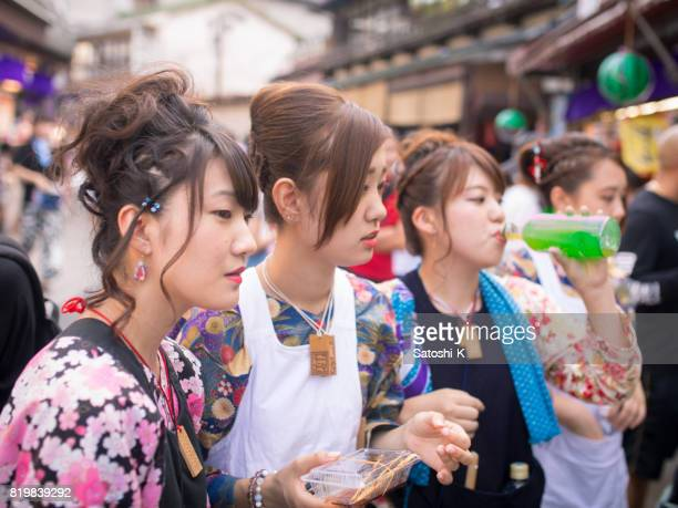 Young women in Japanese matsuri outfit eating and drinking on street