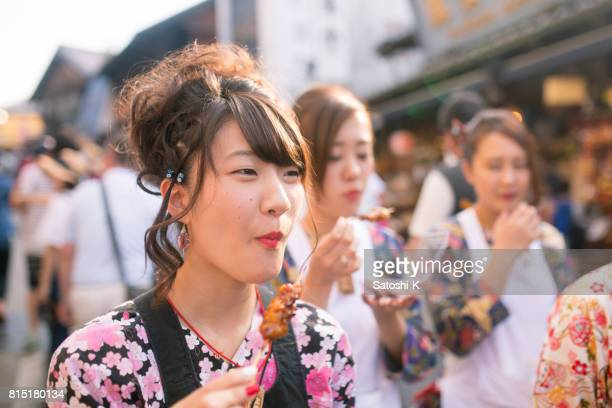 young women in japanese matsuri outfit eating yakitori on street - street fair stock photos and pictures