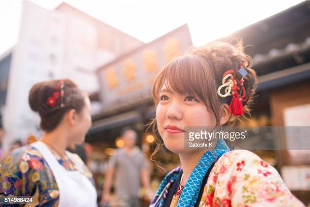 Young women in Japanese matsuri outfit standing on street