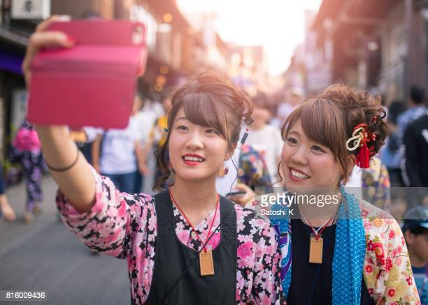 Young women in Japanese matsuri outfit taking selfie picture with toothy smile