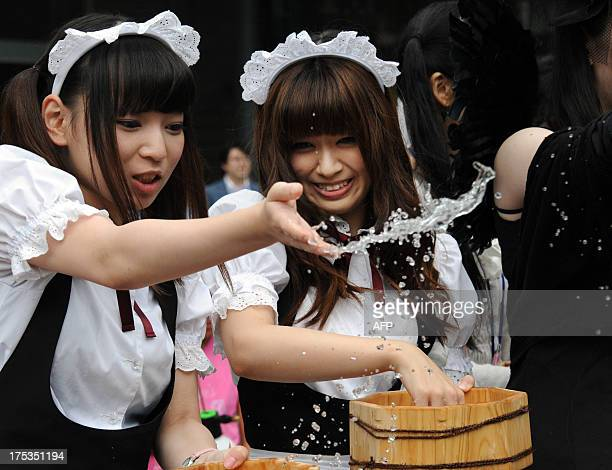 Young women in maid costumes throw water to the ground in Akihabara shopping district in Tokyo on August 3 2013 Over 500 people including 50...