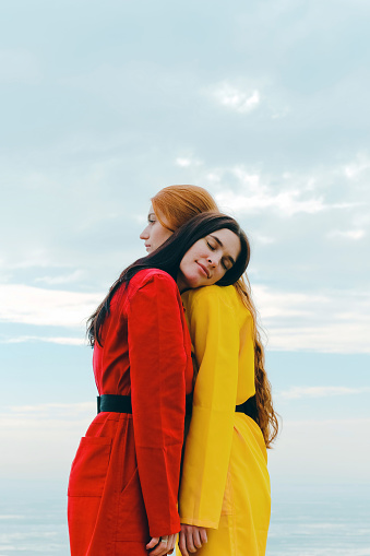 Young women in red and yellow overalls against the winter sky - gettyimageskorea