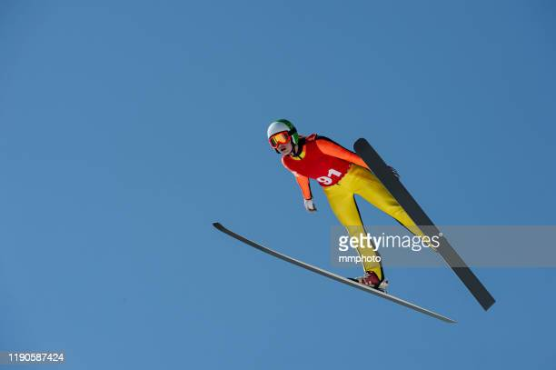 young women in ski jumping action against the blue sky - stunt stock pictures, royalty-free photos & images
