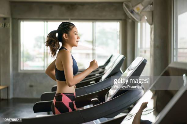 young women in sportswear running on treadmill at gym - スポーツトレーニング ストックフォトと画像