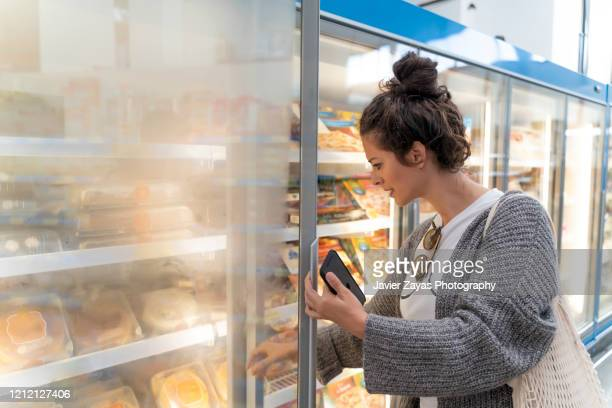 young women in supermarket grocery shopping - frozen food stock pictures, royalty-free photos & images