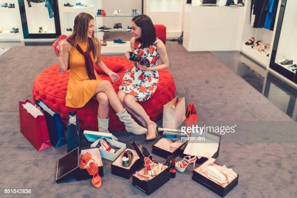 young women in the shopping mall enjoying new shoes - shoe store stock pictures, royalty-free photos & images