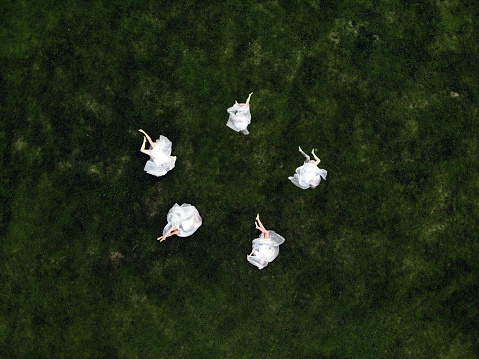 Young women in white plastic lie on a background of green grass. View from above - gettyimageskorea