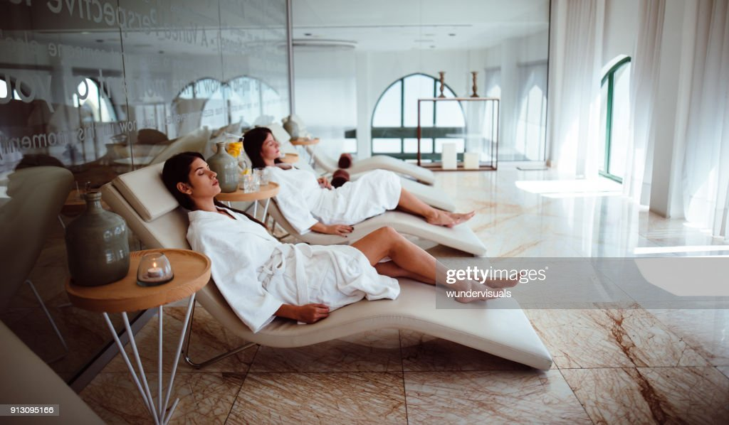 Young women in white robes relaxing at beauty spa centre : Stock Photo
