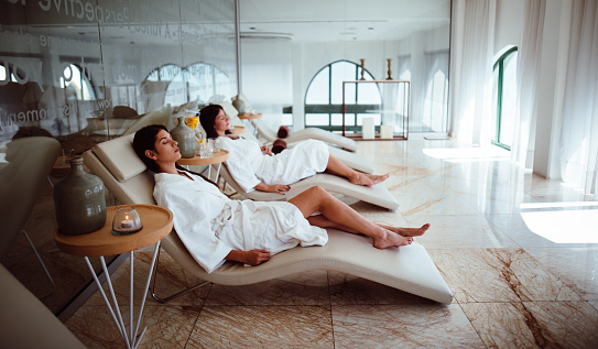 Young women in white robes relaxing at beauty spa centre 913095166
