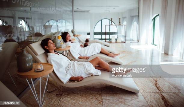 young women in white robes relaxing at beauty spa centre - hotel stock pictures, royalty-free photos & images