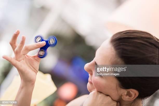 Junge Frauen spielt mit Fidget Spinner im Café.