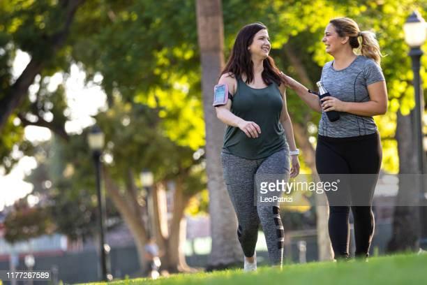 jonge vrouwen joggen en gezond te krijgen in het park - afvallen stockfoto's en -beelden