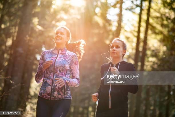 jonge vrouwen die samen joggen in woodland - lange mouwen stockfoto's en -beelden