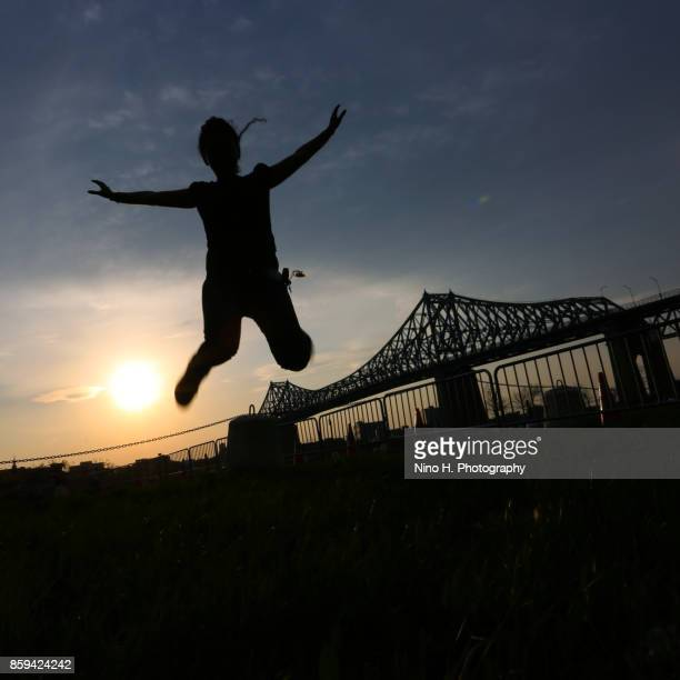Young women jumping and in the background Jacques Cartier bridge