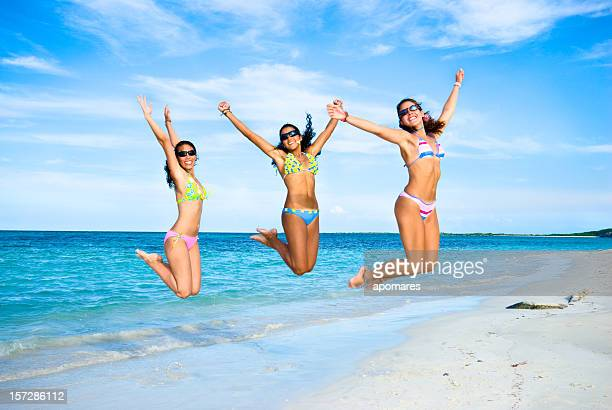 young women jumping in a beach - afro caribbean ethnicity stock pictures, royalty-free photos & images