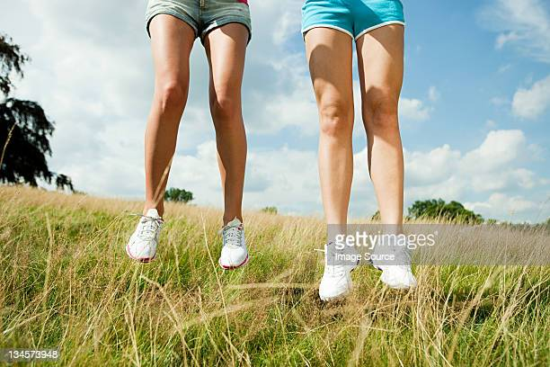 young women jumping in a field - knees together stock photos and pictures
