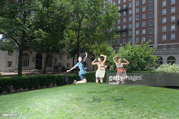 Young women jumping in air at park