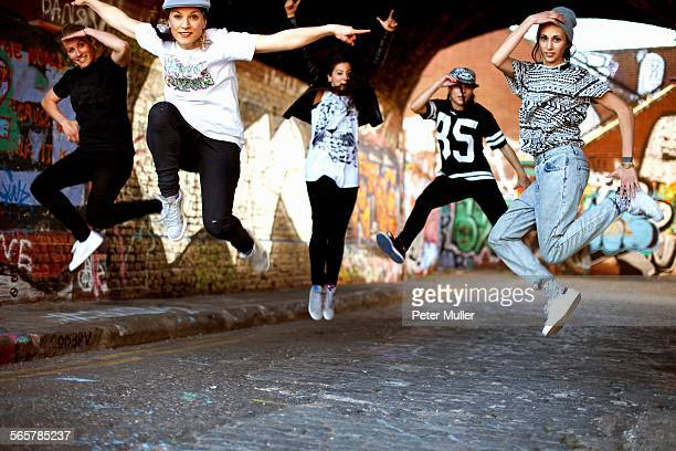 young women jumping in mid air - besatzung stock-fotos und bilder
