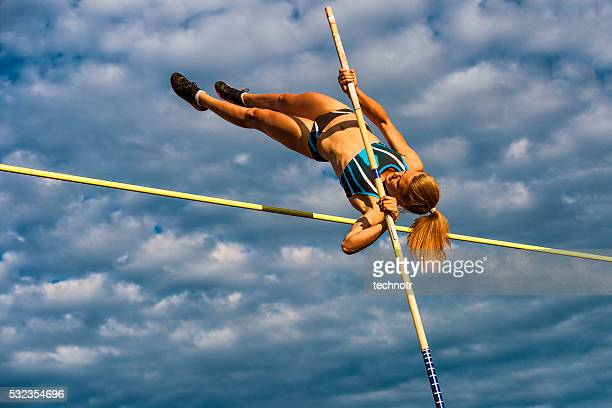 young women jumping over the lath against cloudy sky - athletics stock photos and pictures