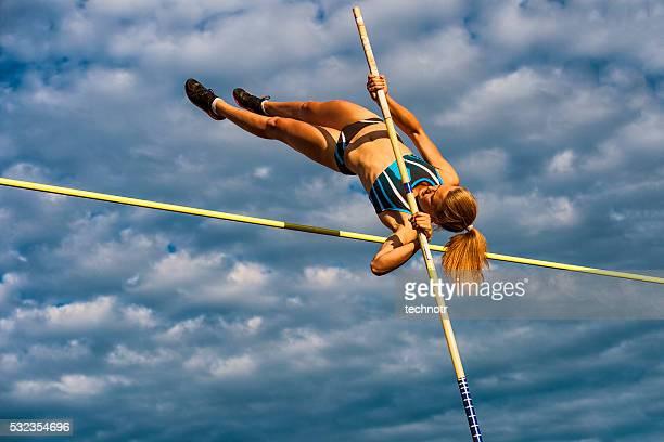 jovem mulher pulando o lath contra o céu nublado - atletismo - fotografias e filmes do acervo