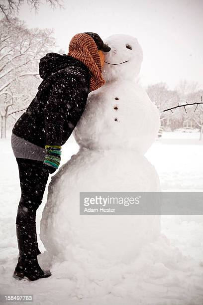 A young women kissing a snowman in the snow.