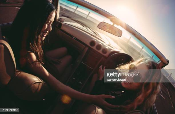 Young women laughing in a convertible on seaside at sunset