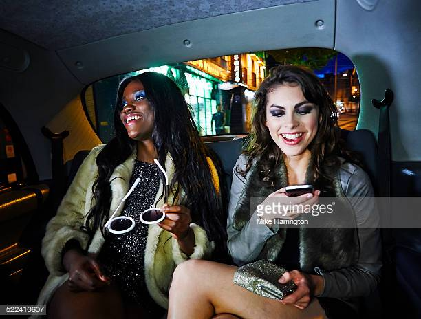 Young women laughing together in taxi