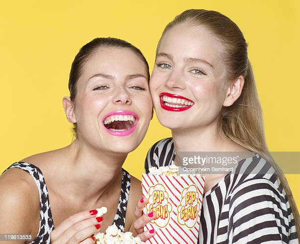 young women laughing whilst eating popcorn