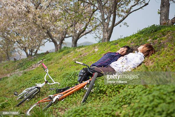 2 young women laying on a grassy hill under a tree