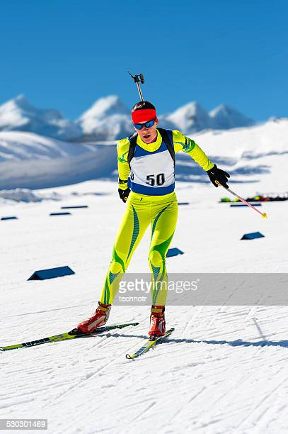 young women leaving shooting range at biathlon competition - langlaufen stockfoto's en -beelden