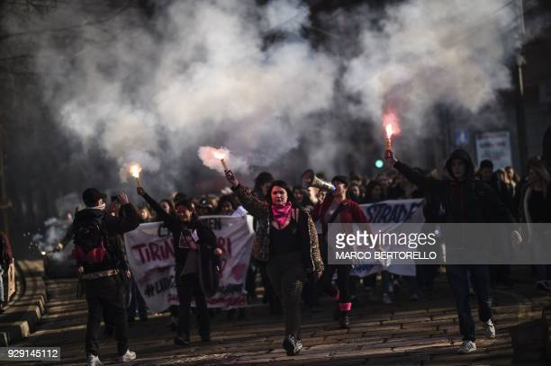 TOPSHOT Young women light flares during the Women March against Violence as part of International Women's day on March 8 2018 in Milan