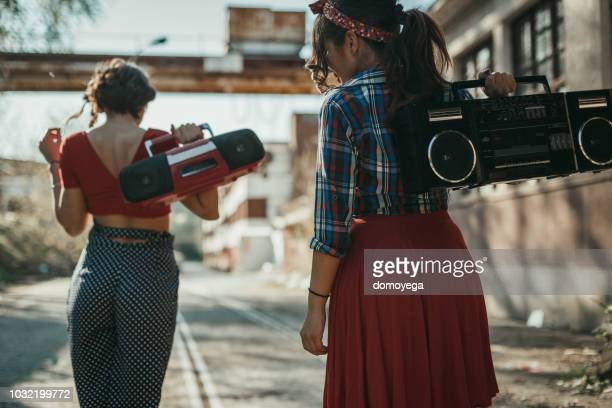 Young women listening to music from a boom box and having fun outdoors