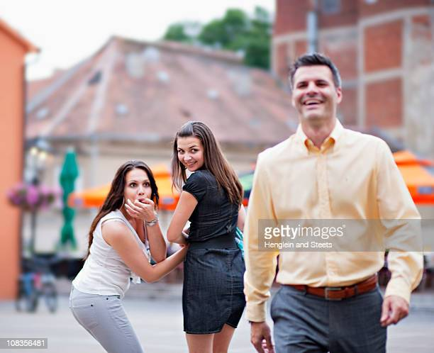 Young women looking after passing man