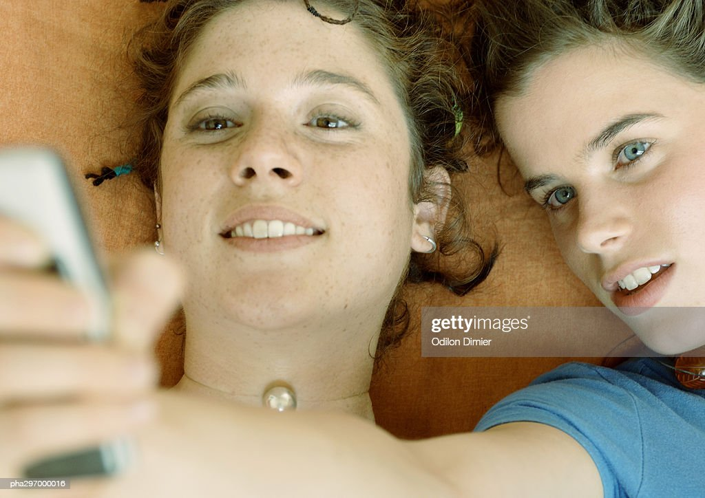 Young women looking at cell phone, close-up : Stockfoto